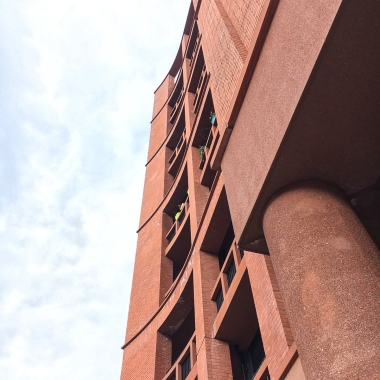 A view of a red sandstone building on a cloudy day